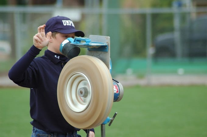 Boy Using Pitching Machine