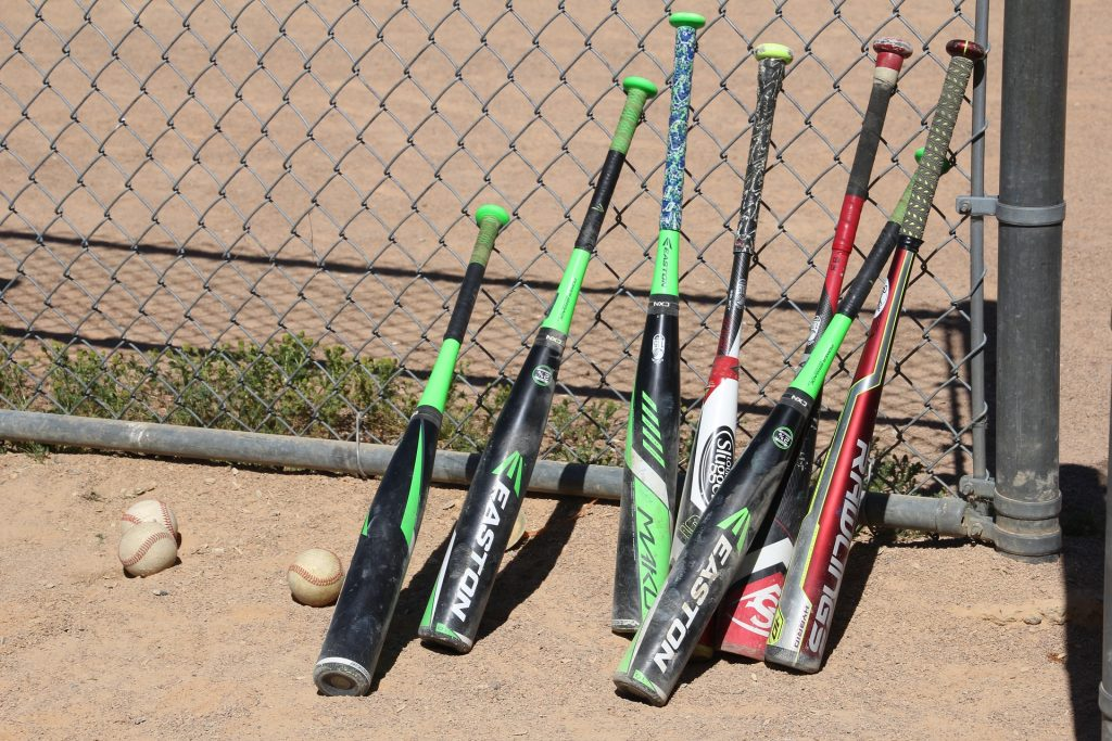 different types of baseball bats lying against a chain-link fence