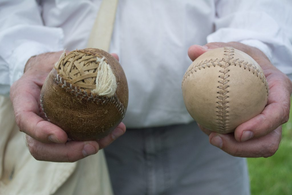 Person holding two old baseballs, one is open showing rubber band on the inside