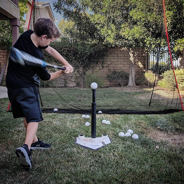 a kid hitting a baseball on a batting tee