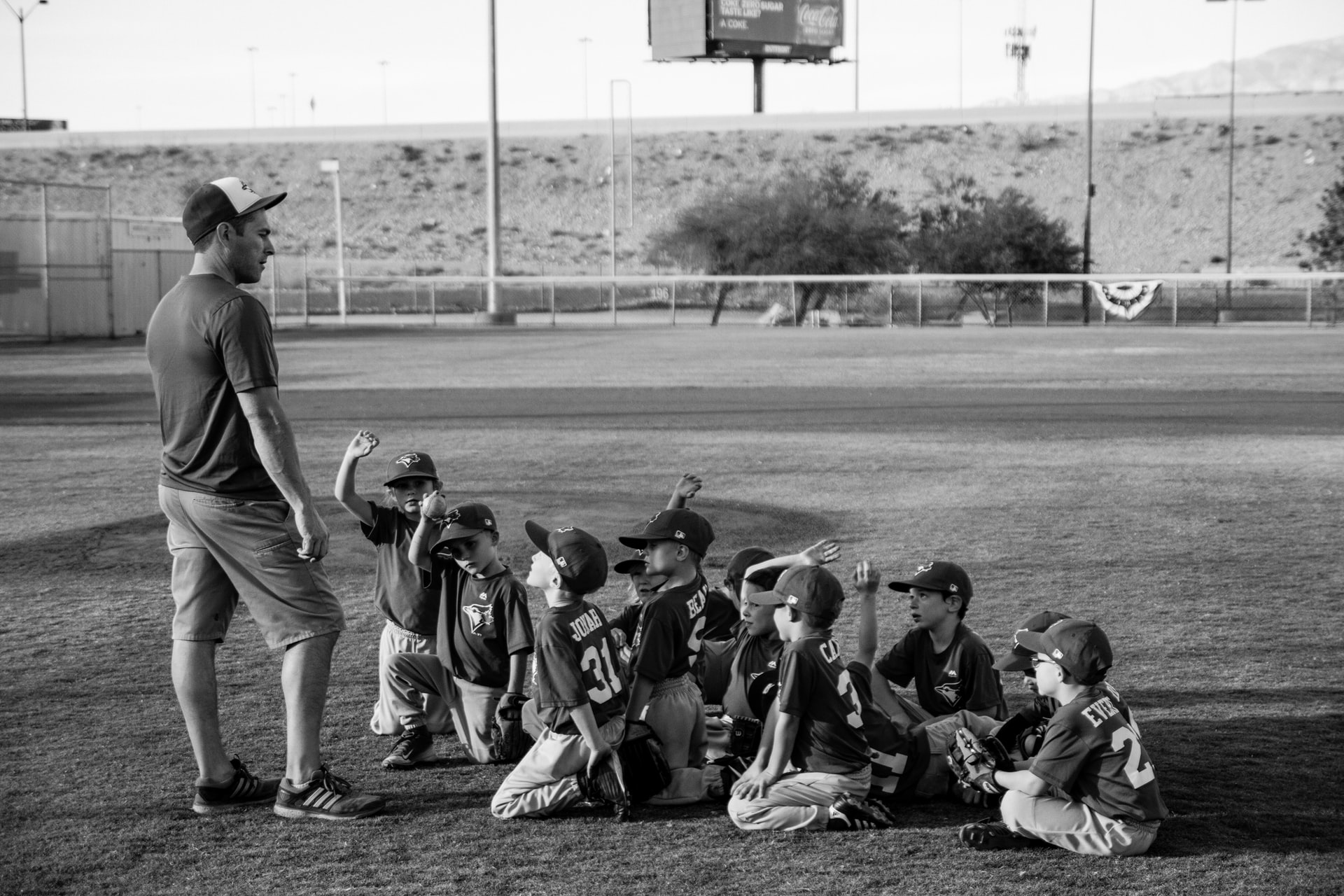 kids seated on the ground learning about baseball from their coach